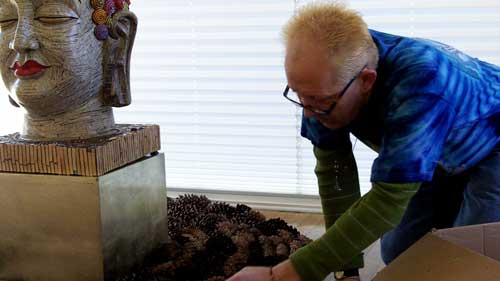 Norm Knott installing Buddha at Charlene's Gallery Ten